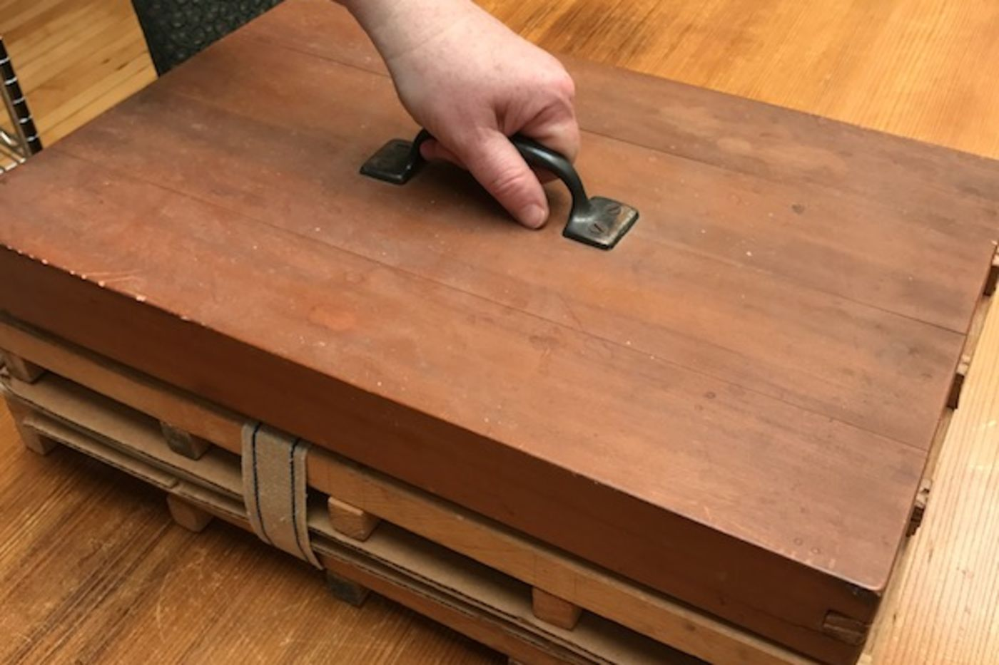 A hand placing a heavy wooden weight with a handle on a wooden stack.