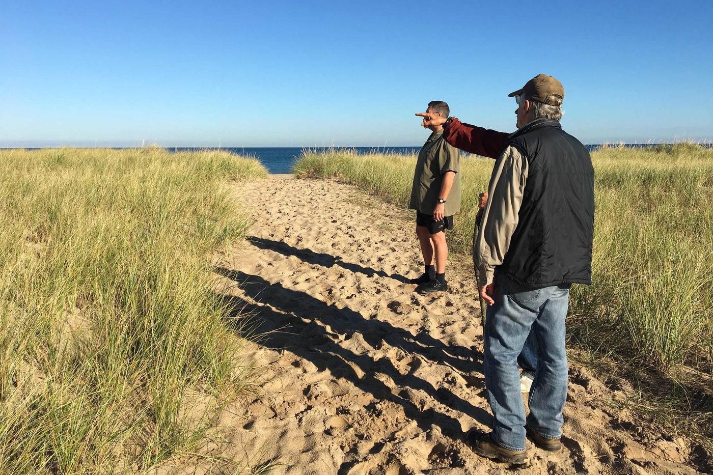 Three people stand on a sandy path that cuts through dune grass on both sides. All three people are looking off to the left and one of them is pointing. They cast long shadows on the sand in front of them. The dark blue water of Lake Michigan is in the background, with lighter blue sky above it.