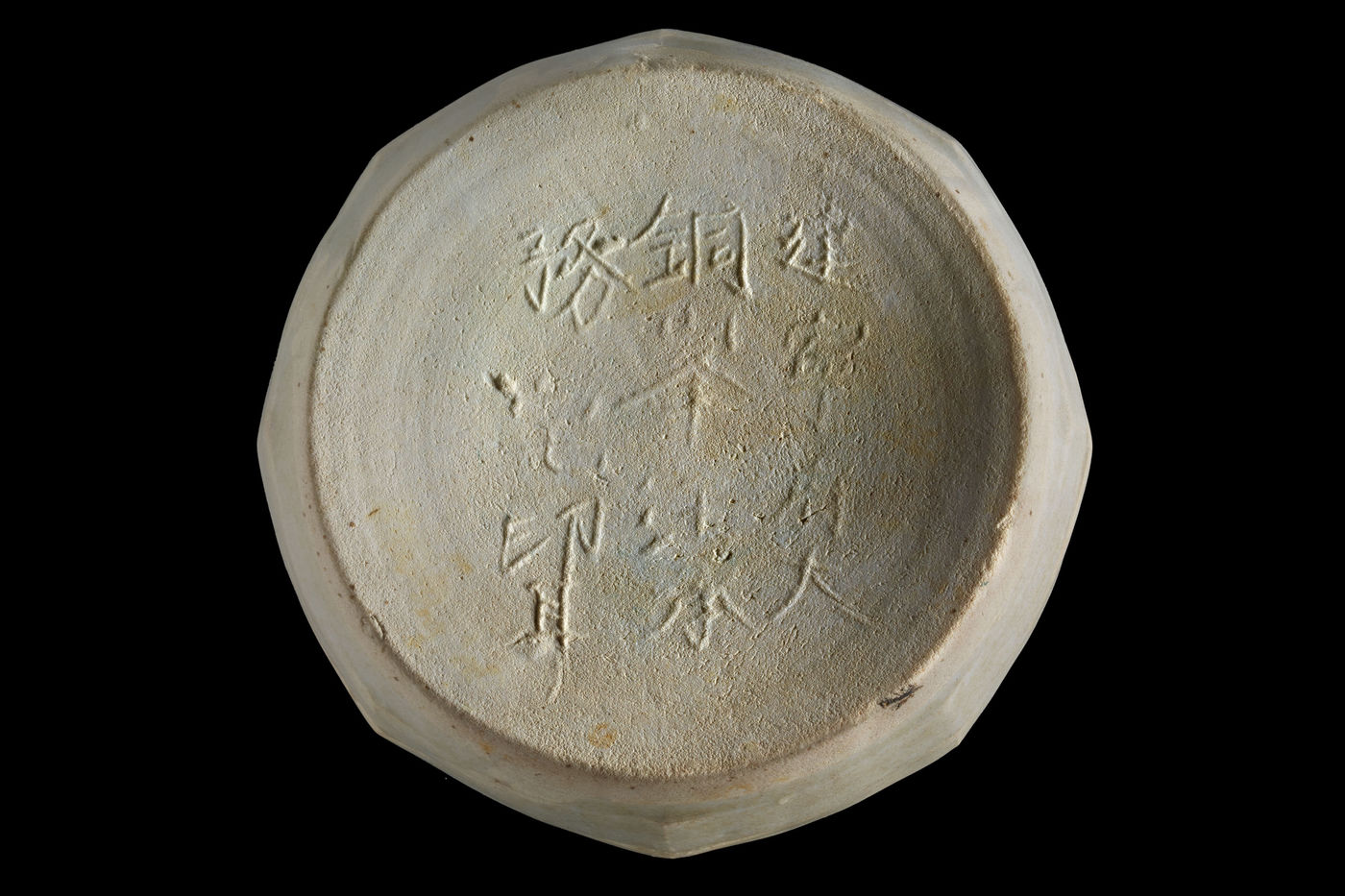 The base of a ceramic container photographed on a black background. There are raised Chinese characters on the base's recessed surface, which is round. Beyond the round edge, it appears as though the body of the container is octagonal in shape.