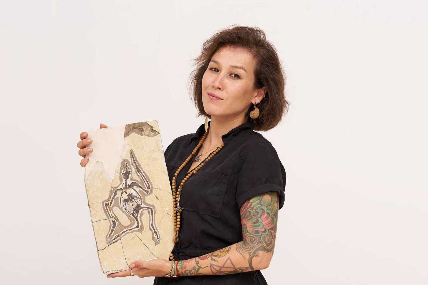 Jingmai O'Connor holding a slab with a small fossil.