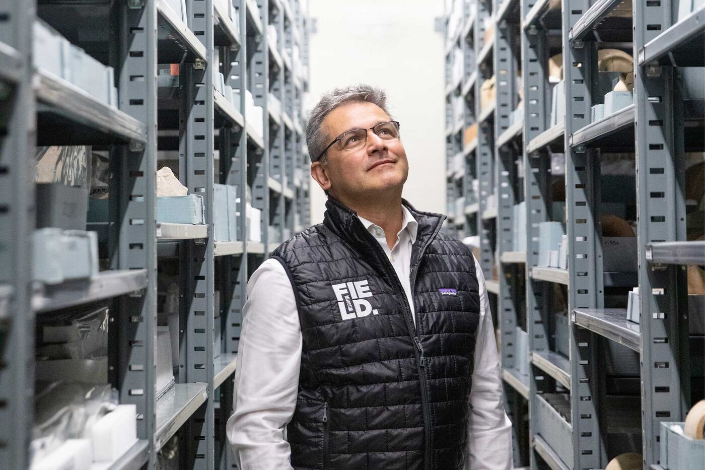 Julian Siggers, wearing a Field Museum vest, stands between two tall shelves that hold museum collections.
