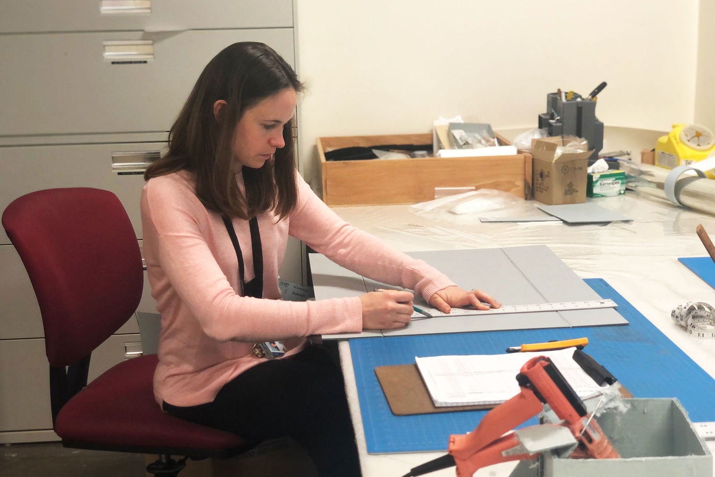 A woman sits at a desk and uses a rule. Other supplies like a hot glue gun and measuring tab sit on the desk.
