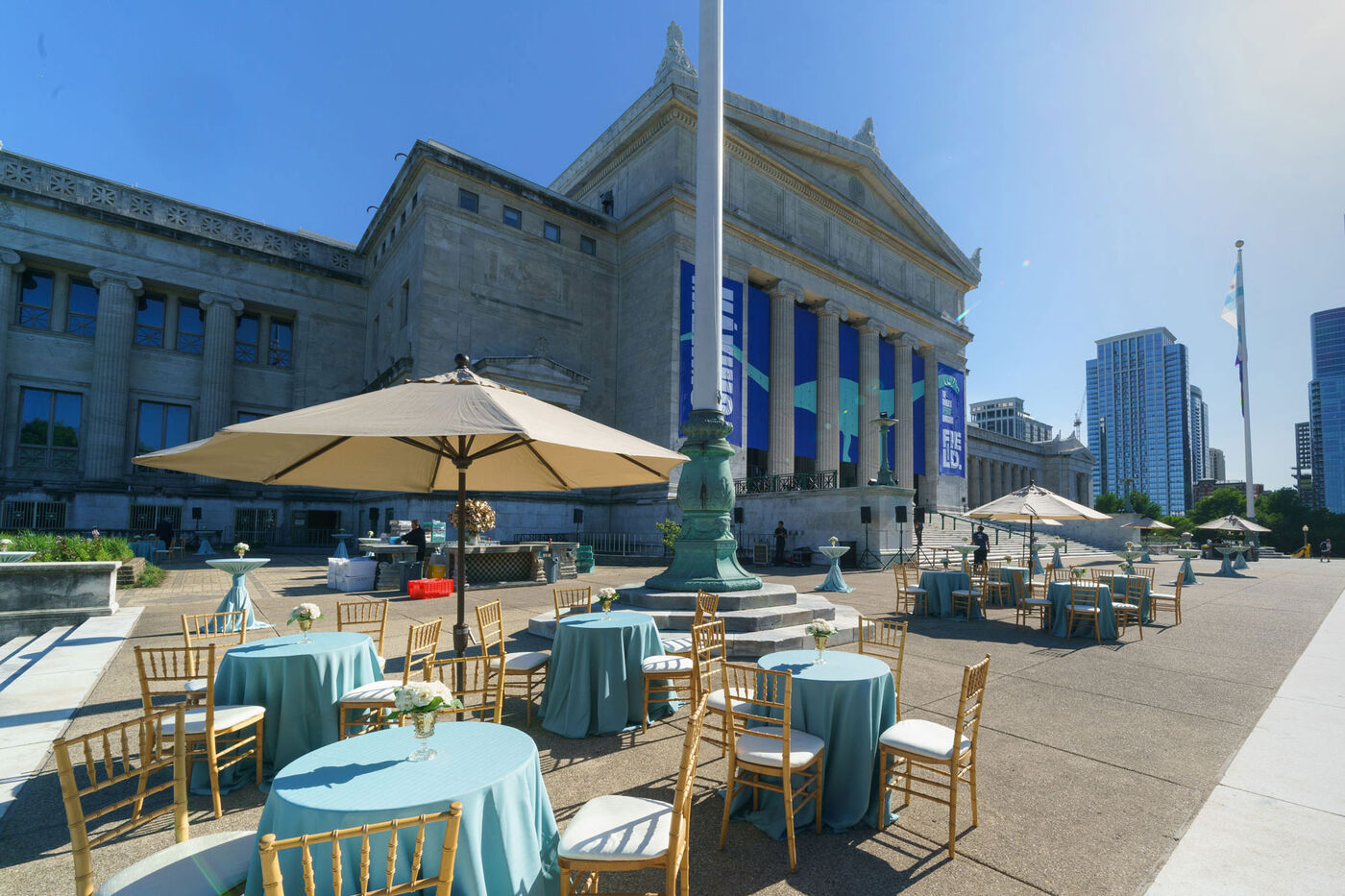 Tables and chairs set up outside the north entrance of the Field Museum on a sunny day.