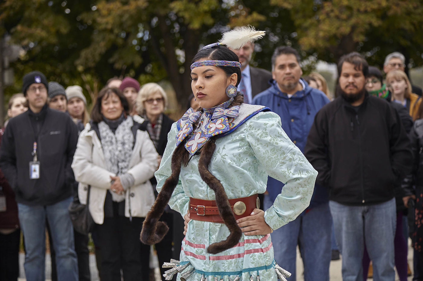 A woman, Maritza Garcia, wearing a light blue dress and a headdress with a feather, performs a dance in front of onlookers at the land acknowledgment ceremony.