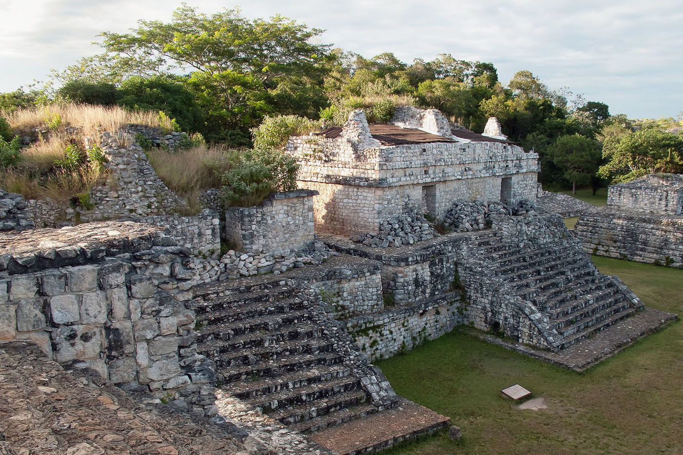 Ruins of ancient structures made out of stones. Two staircases, low walls, and part of a building are still intact.