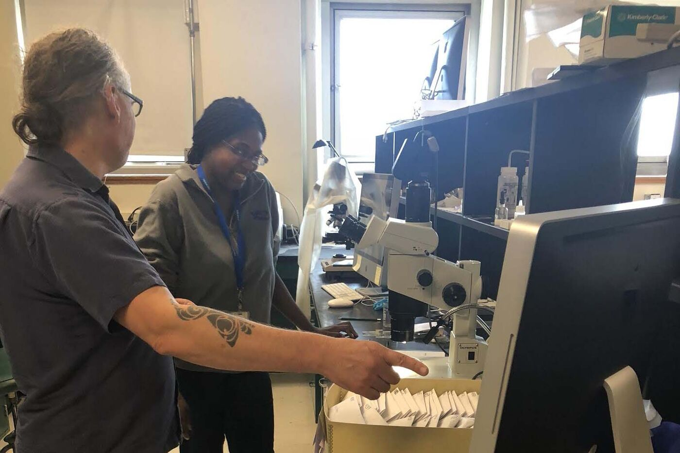 Two researchers reviewing collections materials in a lab.