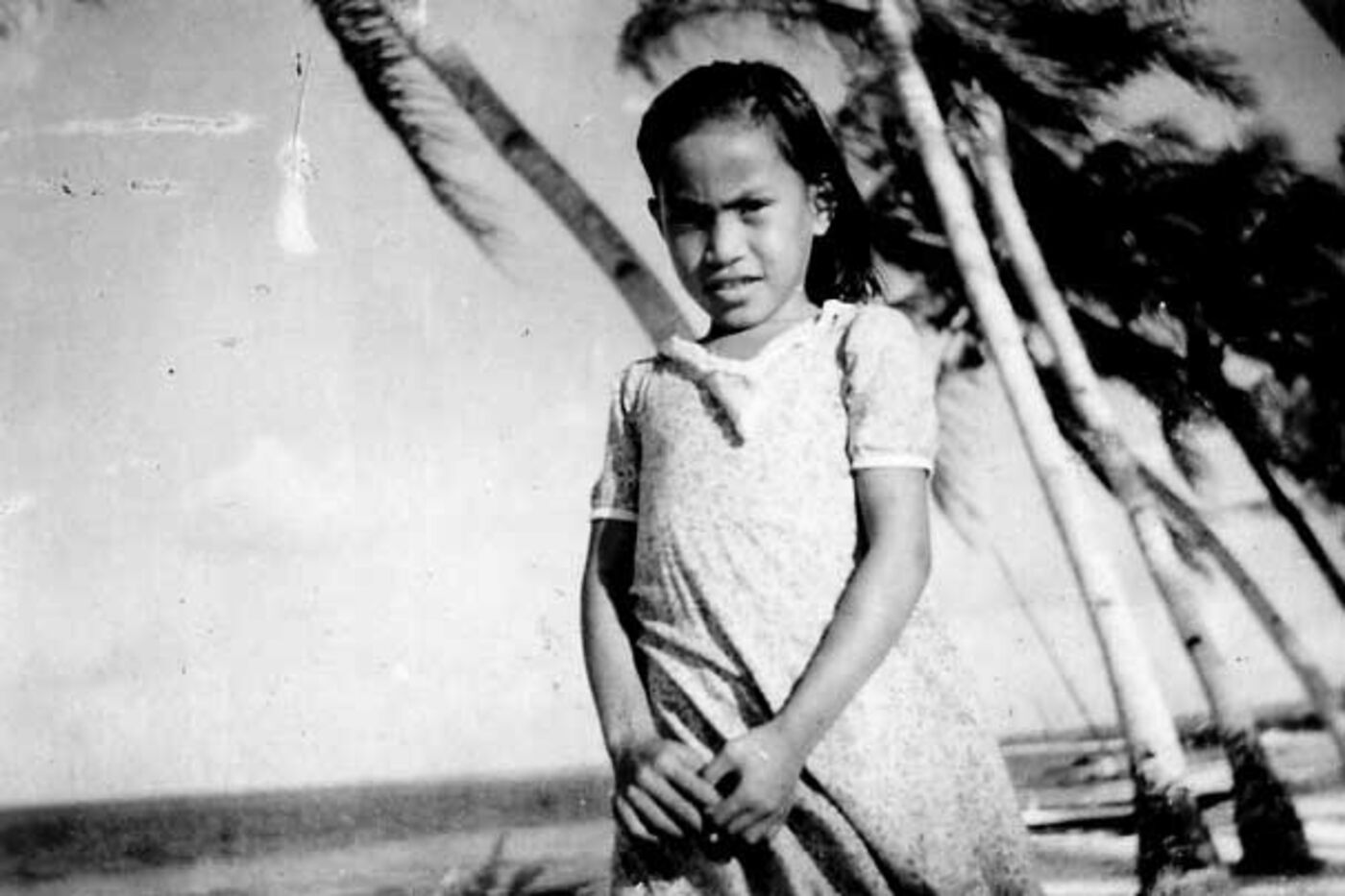Black-and-white photo of a young girl looking at the camera, with palm trees in the background.