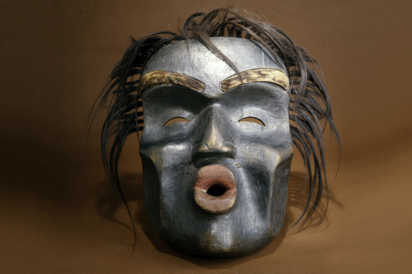 A mask with prominent eyebrows and a large open mouth, as if singing. The black hair looks realistic and frames the face.