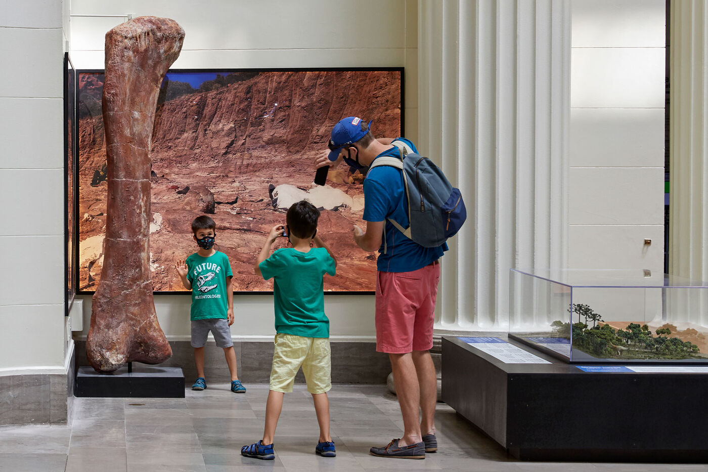 A young boy wearing a face mask poses for a photo next to a dinosaur bone that's twice his height, in front of a mural of a rocky landscape. Another young boy and a man take his photo.