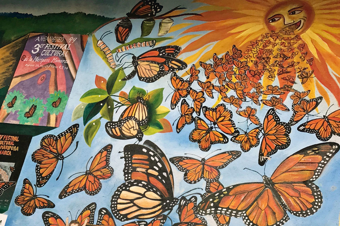 A painted mural shows the sun with a face, and orange and black monarch butterflies flying out of its mouth. The monarch life cycle is also depicted, showing caterpillars and chrysalises.