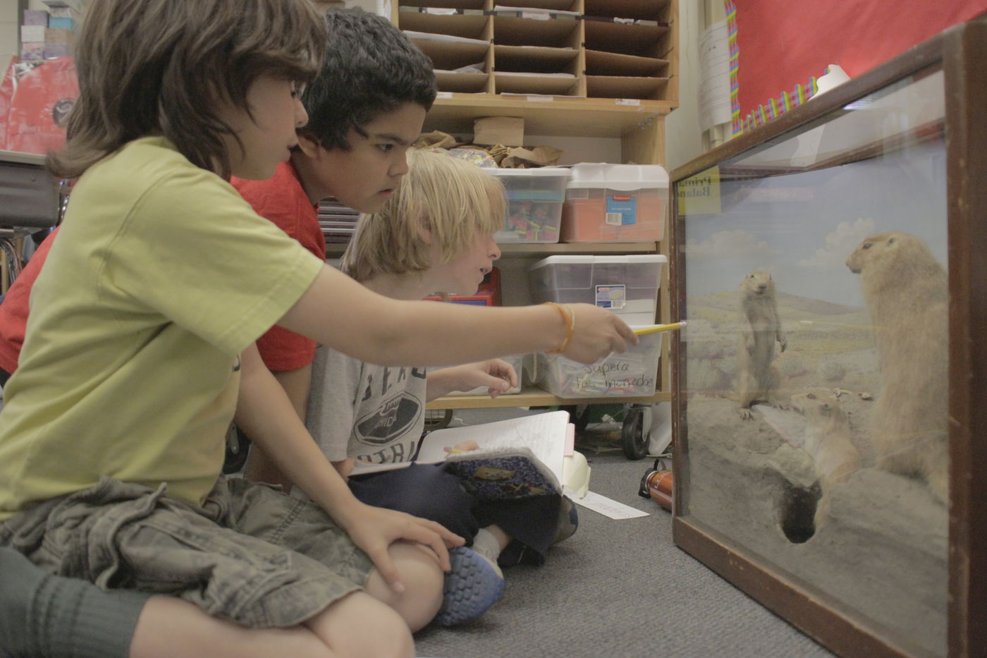Three students, one pointing with a pencil, intently looking at a portable museum display case.