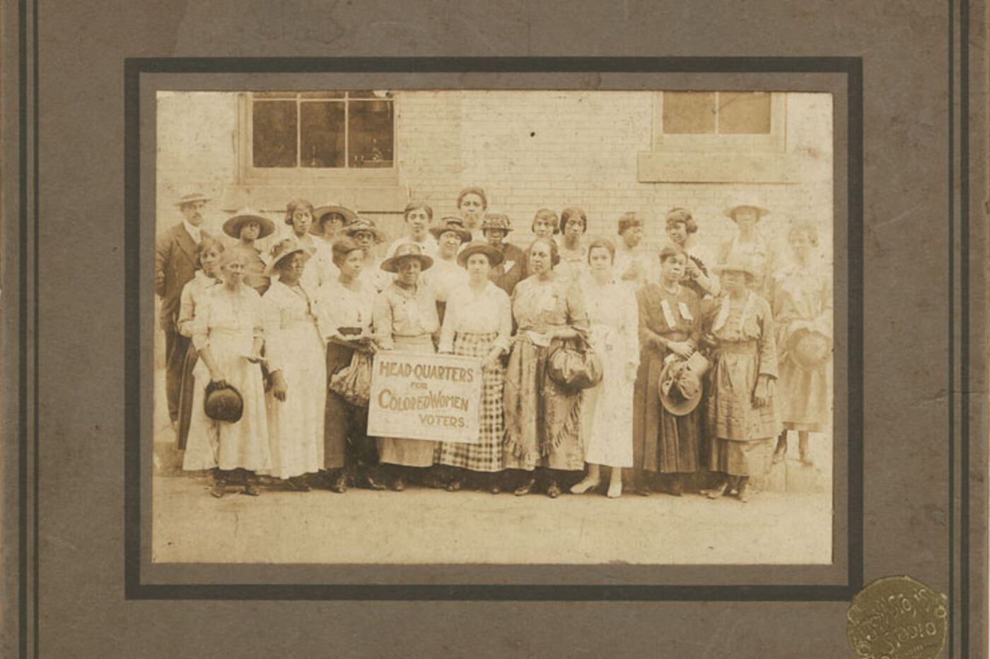 """A group of women pose in front of a building. Two women in the front hold a sign that reads, """"Head-Quarters for Colored Women Voters."""""""