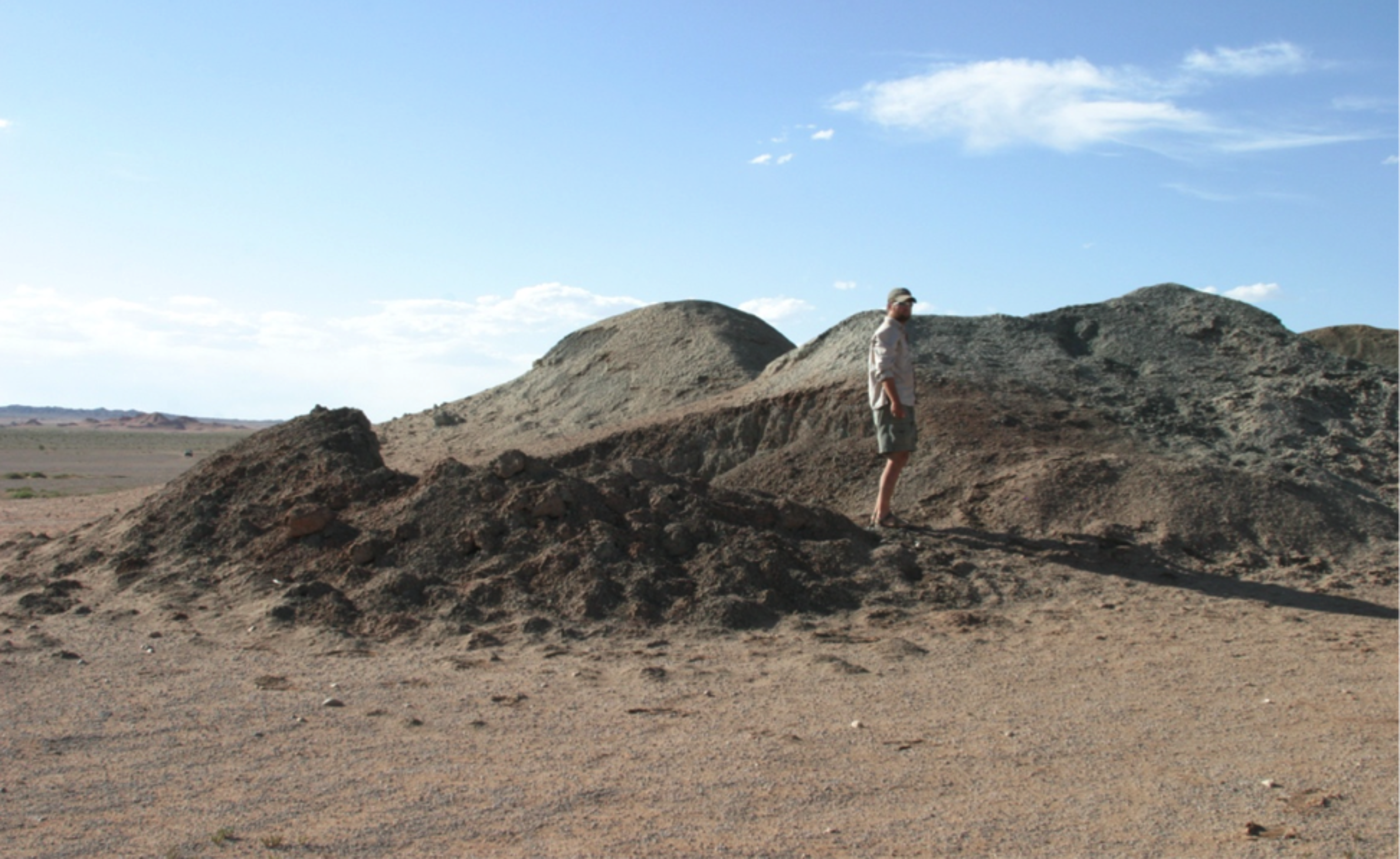 A man standing in a desert-like landscape, under blue sky and clouds