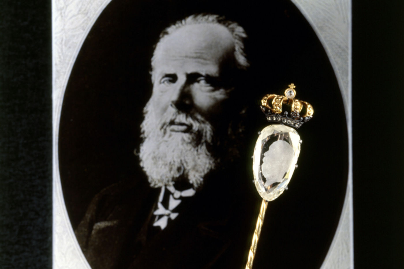 A very large diamond with a bearded man's profile carved into it (King William II of Holland). The diamond has a gold crown affixed to the top. A photograph of the same man is seen in the background.
