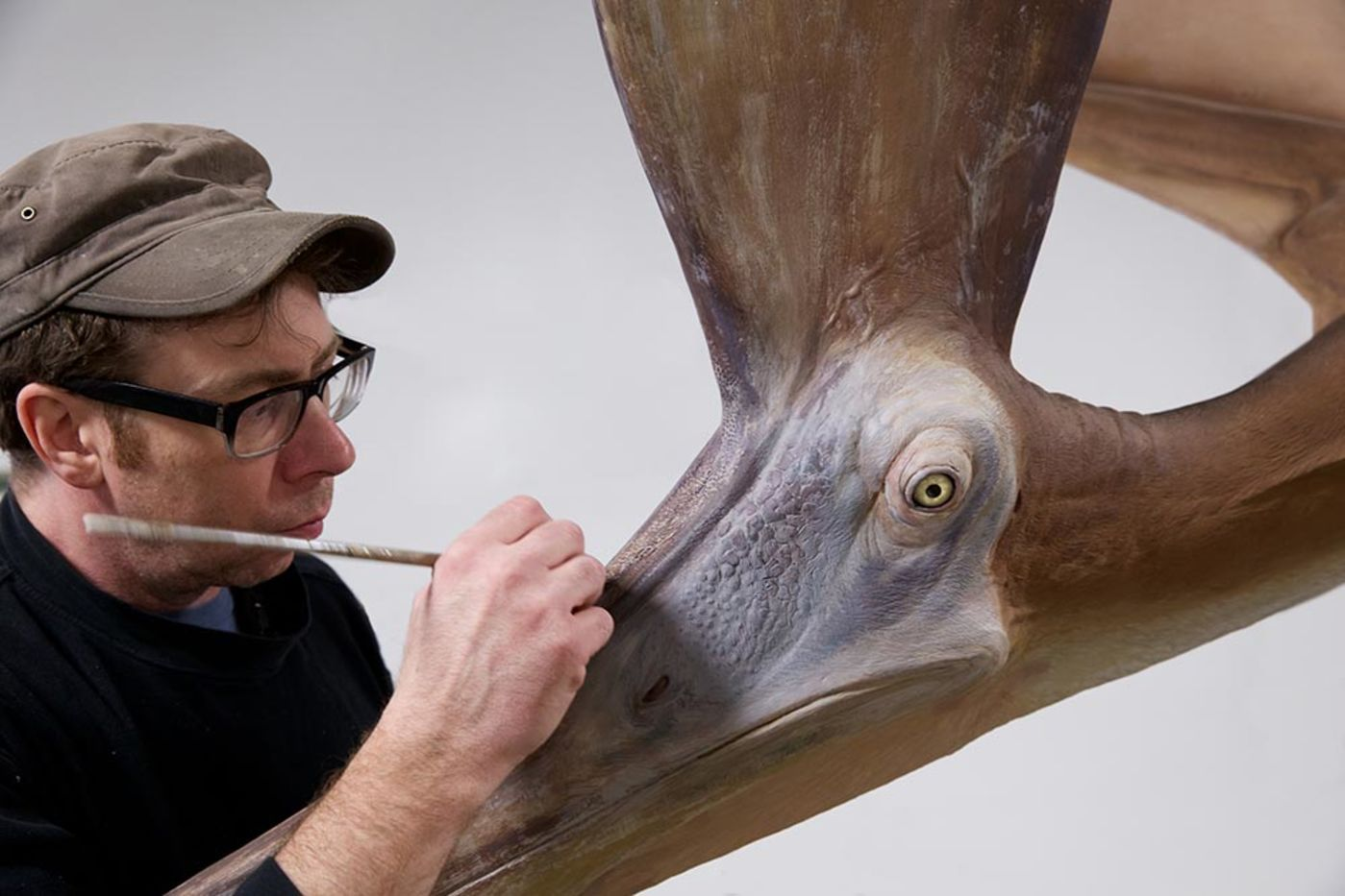 Close-up photo of a man painting the beak of a lifelike giant reptile