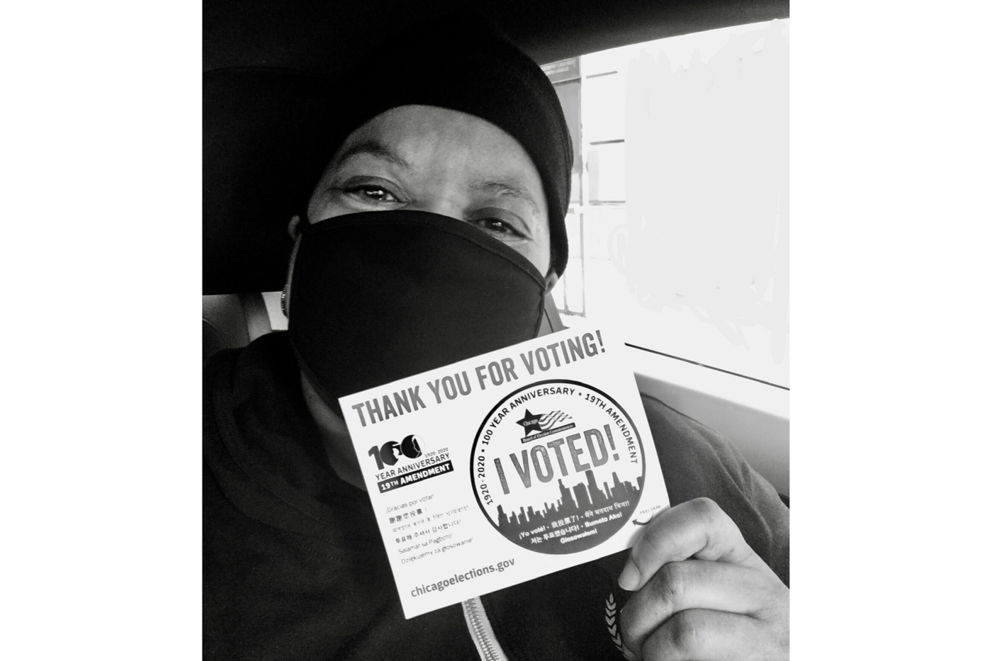 """Reda Brooks, wearing a face mask, holds up an """"I voted!"""" card."""