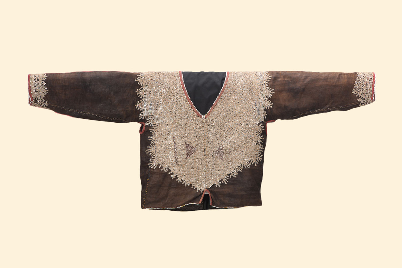 Man's jacket, mostly brown in color, with a v-shaped neckline. Embroidery in a lighter color covers the jacket's chest and decorates the area of the sleeves worn around the wearer's wrists.