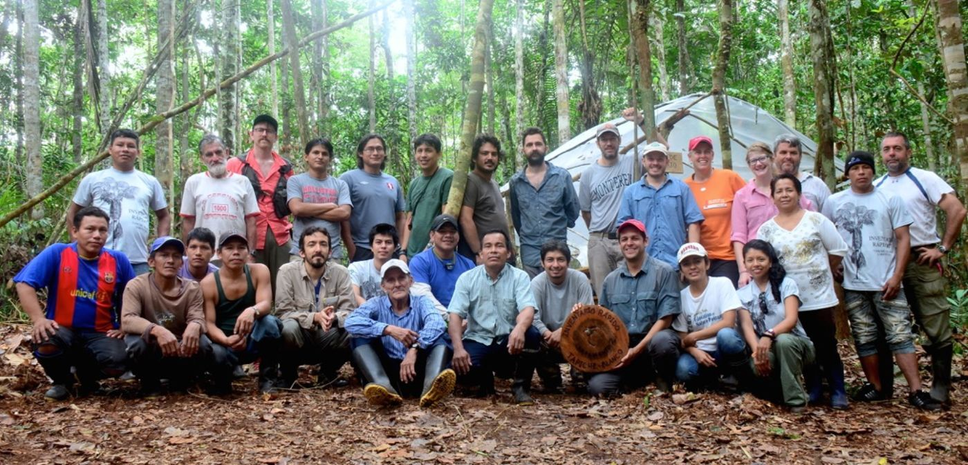 Two rows of people posing for a photo, with a forest visible in the background