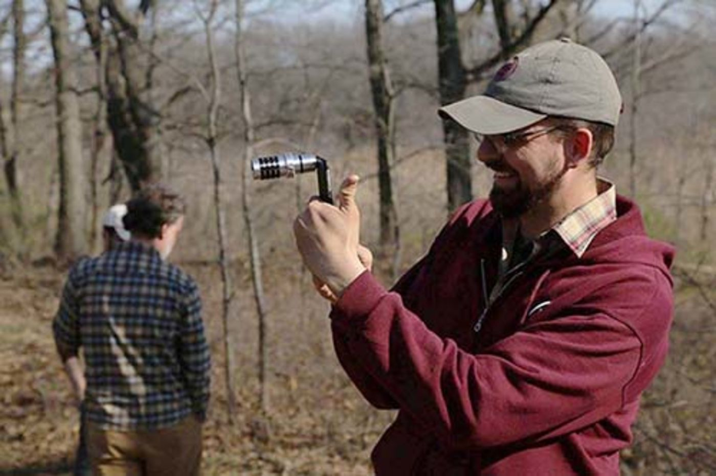 A man in a wooded area taking a photo with a zoom lens