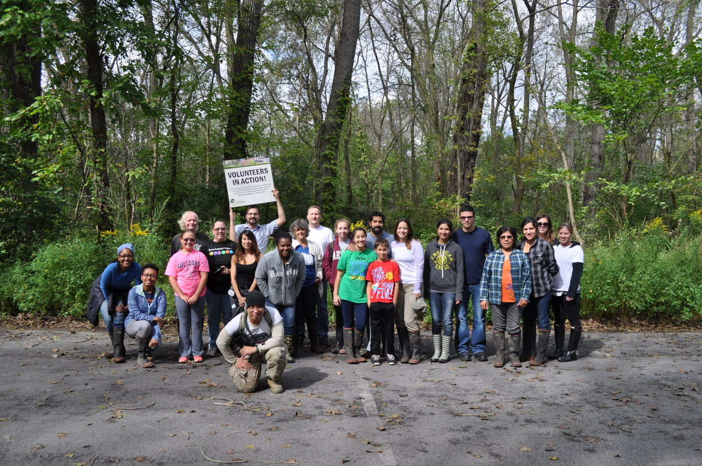 """Habitat restoration volunteers of all ages gather for a photo in a wooded area. One person holds up a """"Volunteers in Action"""" sign."""