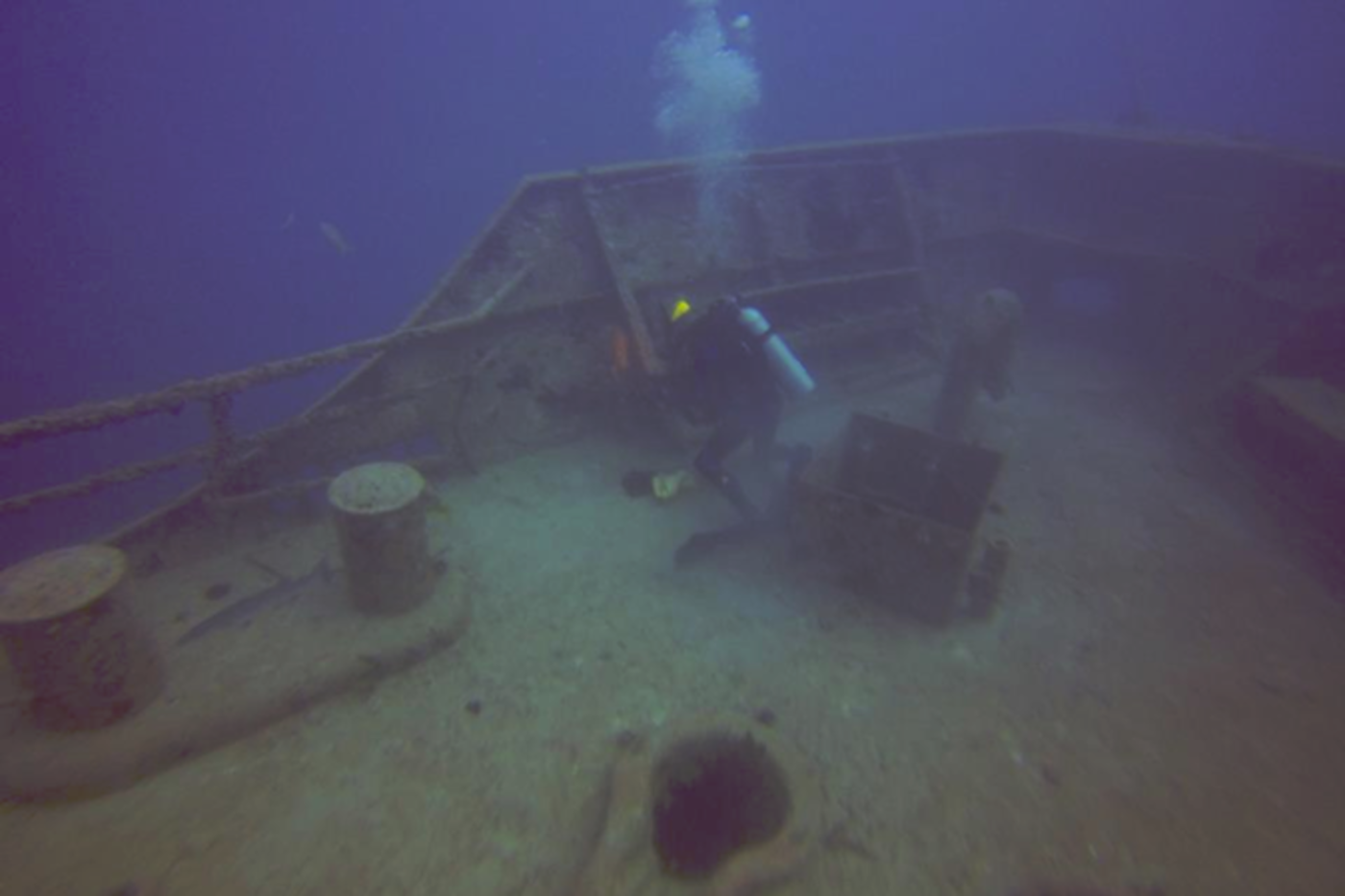 A scuba diver on the deck of a submerged boat