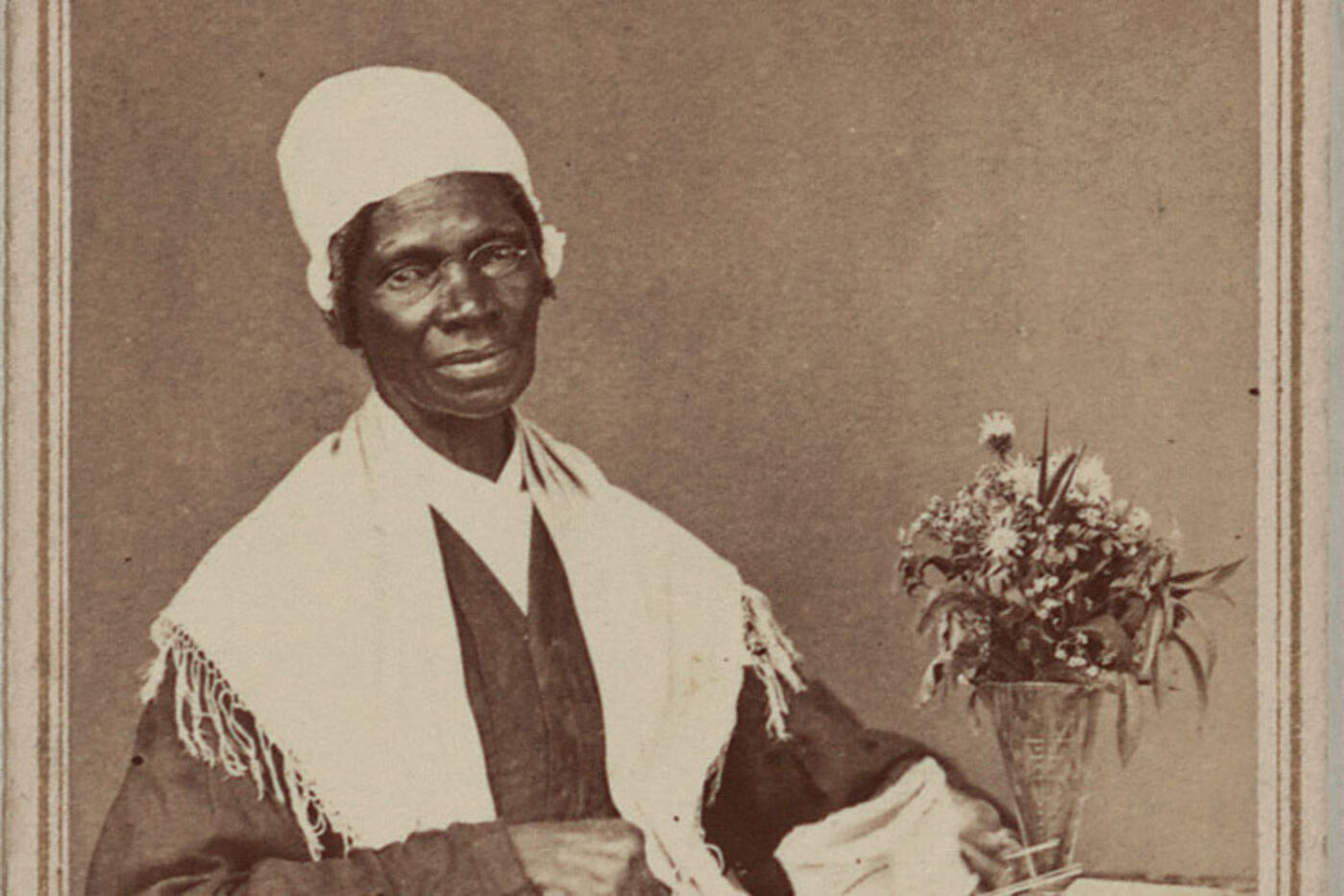 Portrait of Sojourner Truth, seated next to a vase of flowers.