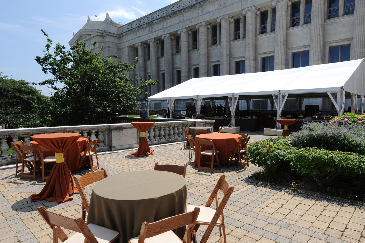 Tables set up on Field Museum's outdoor terrace. A tented area is visible in the background.