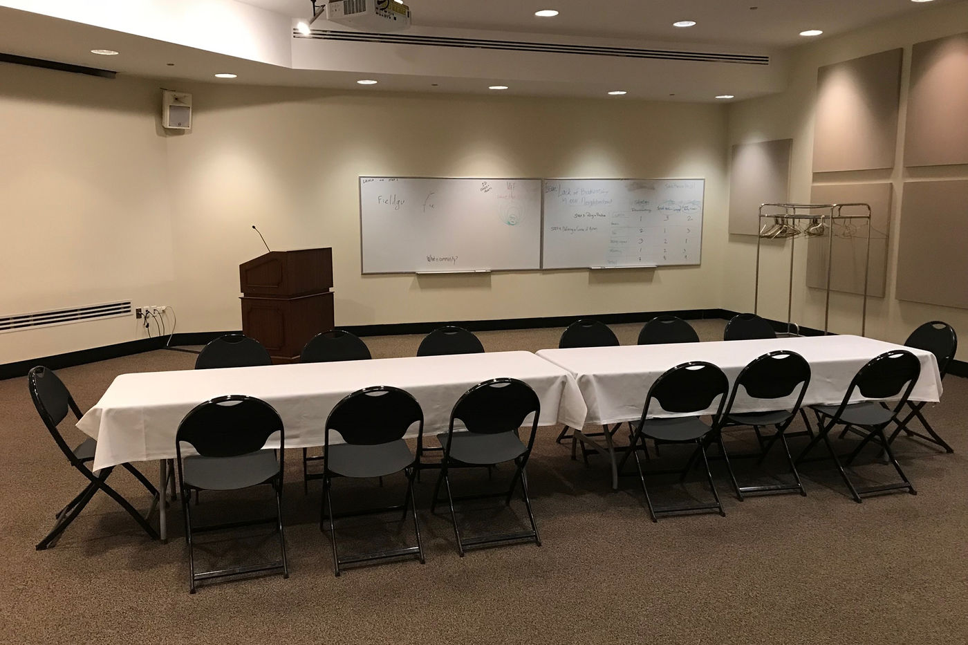 A long tables sits in the middle of Lecture Hall II. The table is set for 14 guests and topped with a white tablecloth. A podium, two whiteboards, and empty coat rack are visible in the back. A projector hangs overhead.