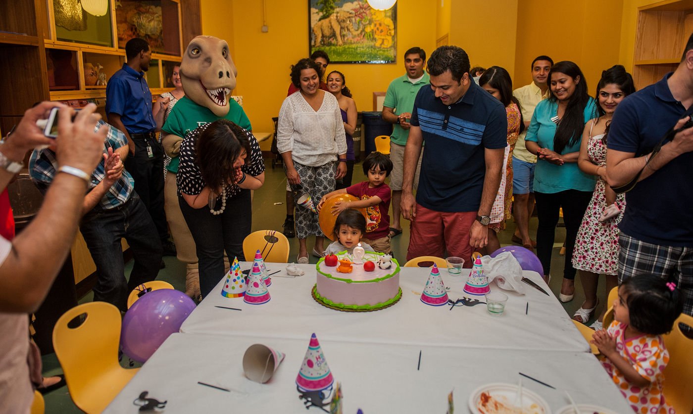 A family celebrates a birthday party in the Art Studio of the Crown Family PlayLab. The group is smiling at a toddler who sits at the end of a table in front of a birthday cake. Cups, napkins, and birthday party hats are scattered on top of the table. A T. rex mascot stands with the crowd.