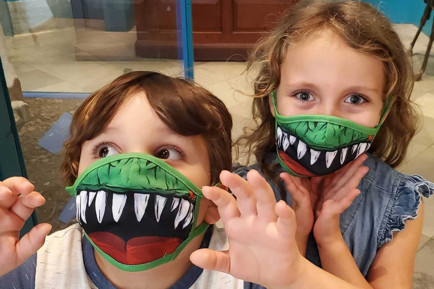 Two kids wearing dinosaur face masks.
