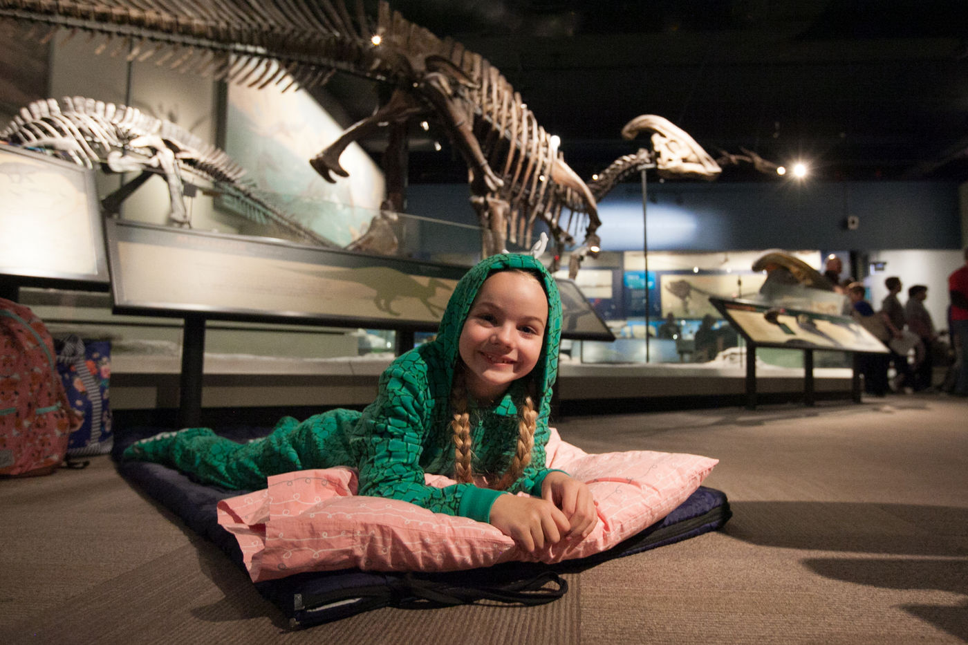 Young girl smiles to the camera while laying atop a sleeping bag in the Elizabeth Morse Genius Hall of Dinosaurs. A Parasaurolophus fossil stands in the back.