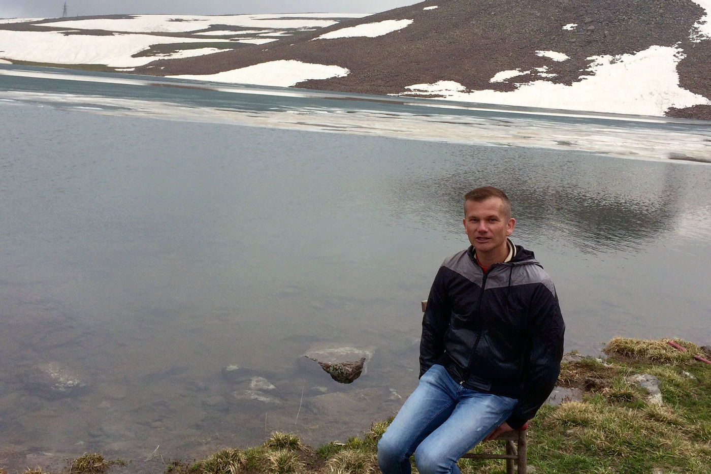 A man sitting on a chair in front of a river, with a snowy glacier in the background.