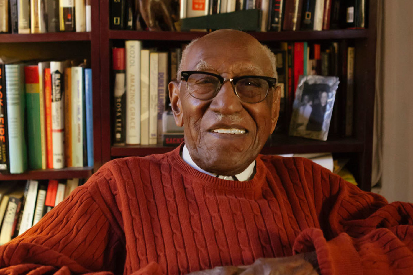 Timuel Black, smiling, sits in front of a bookshelf in his home. He wears black browline style glasses, a white collared shirt, and a red sweater.