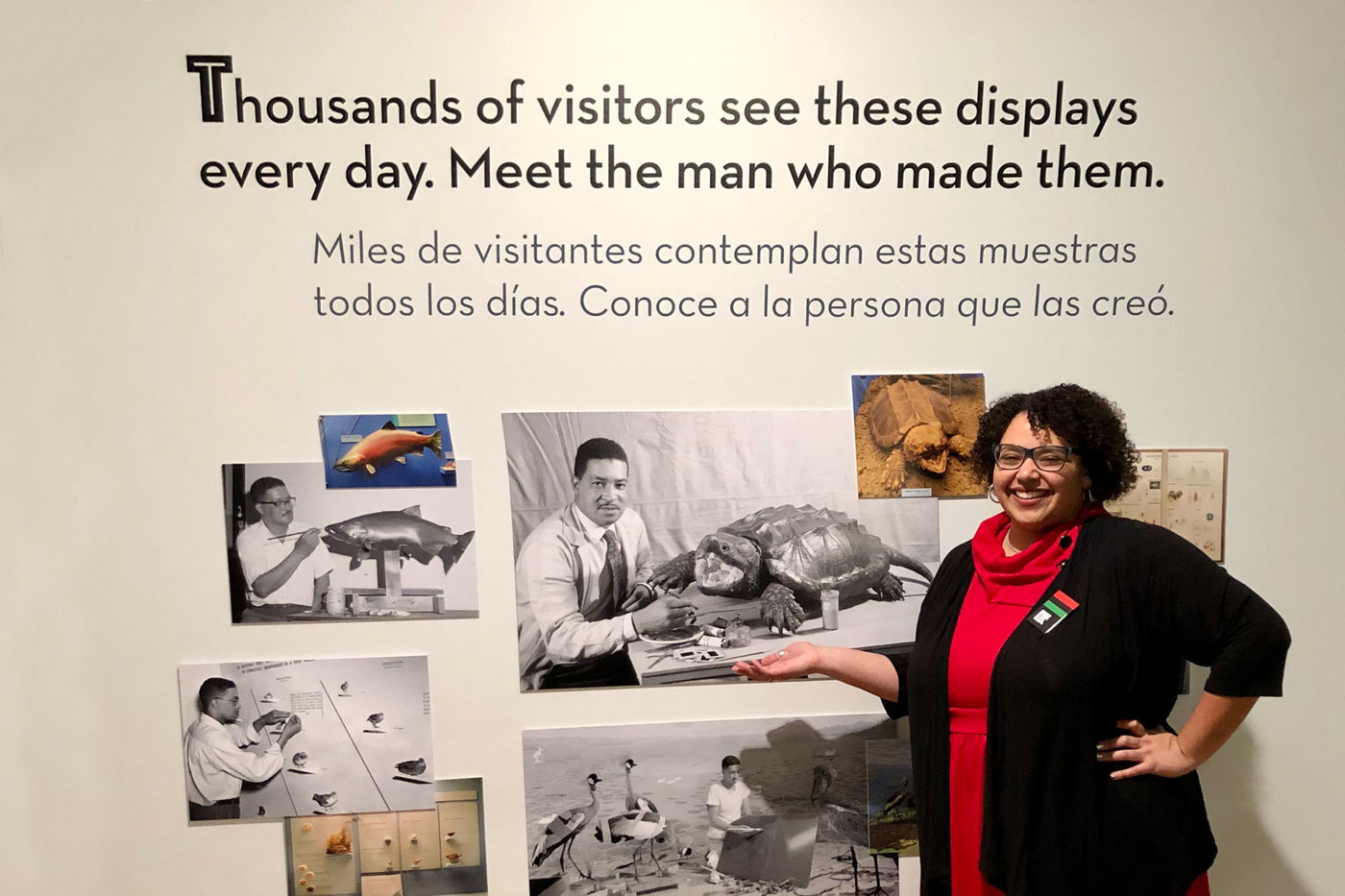 "Tori Lee stands in front of a wall of photos of Carl Cotton. Text on the wall above the photos reads, ""Thousands of visitors see these displays every day. Meet the man who made them."""