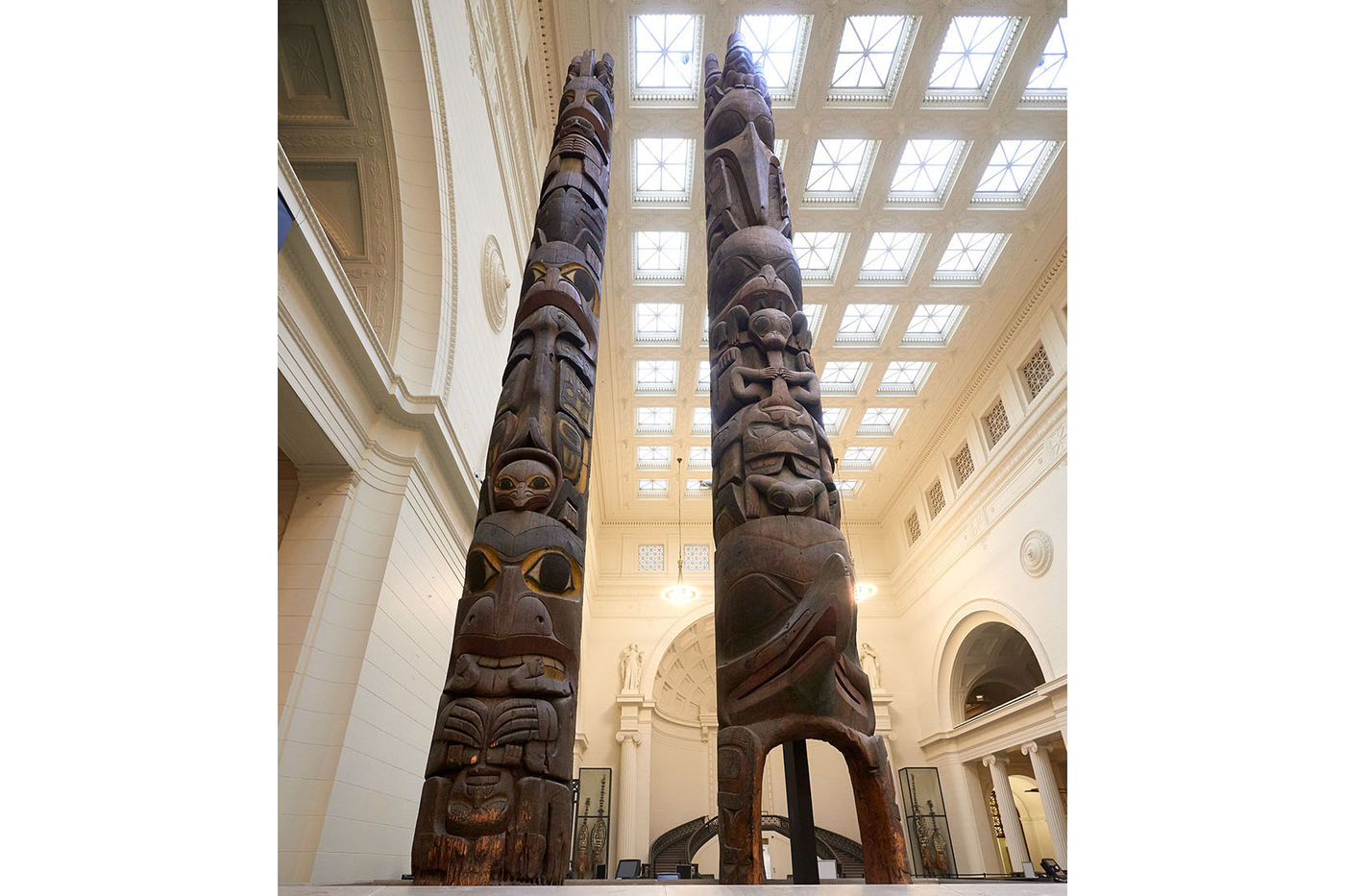 Looking up at two wooden totem poles standing side by side in the museum's main hall, with skylights in the ceiling in the background. The poles are intricately carved with a variety of human and animal faces, and some small patches of paint are visible.