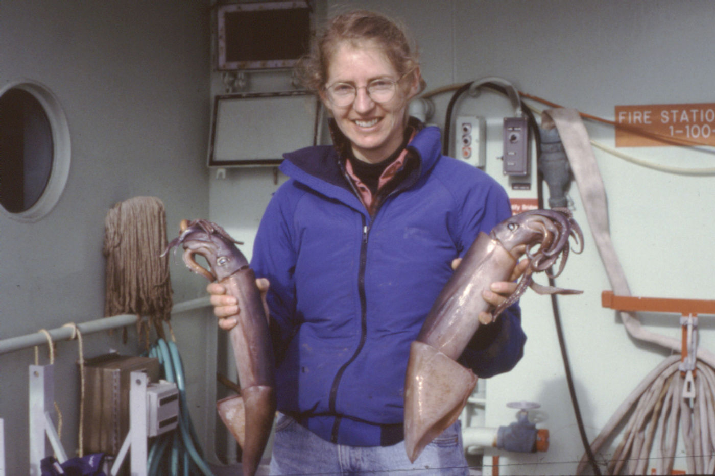 A woman wearing waterproof gear stands on a boat and holds a purple-silver squid in each hand.