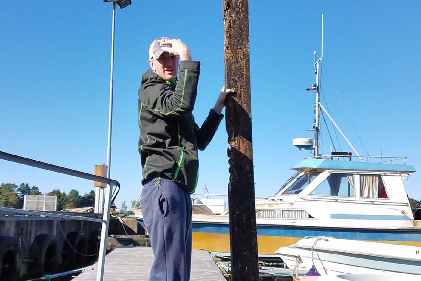 A man standing on a dock holding up a wooden pillar taller than he is, in front of boats and with a bright blue sky background.