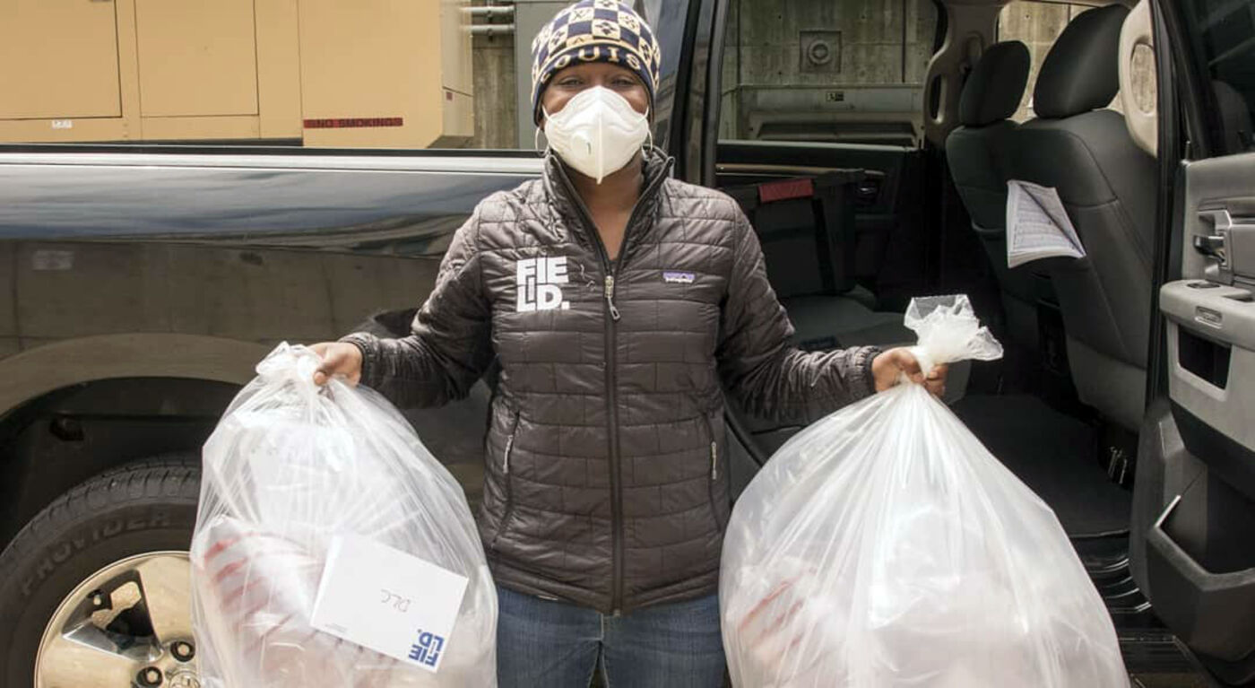 Ylanda Wilhite, wearing a facemask, holds two large bags full of face shields that are ready to load into a car behind her.