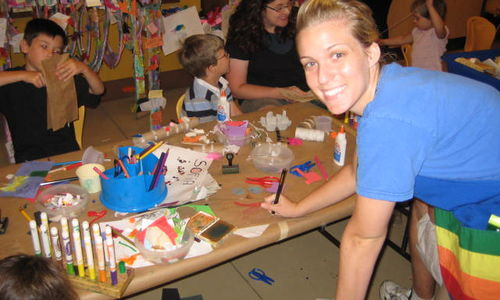 Volunteer smiles while working with children in the Crown Family PlayLab