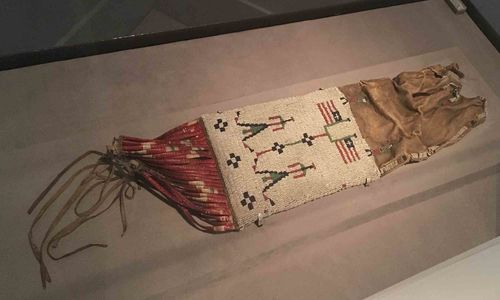 Brown, white, and red beaded bag with design of two people standing next to two flags