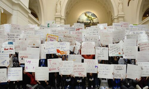 A group of about 150 people holding up signs with writing on them, inside a Neoclassical-style building