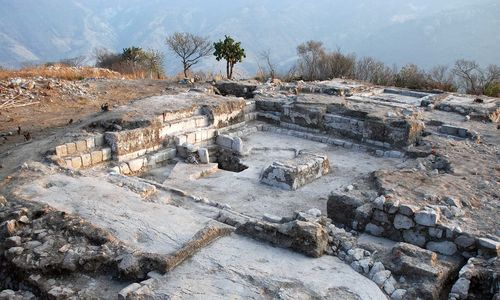 Archaeological ruins in the outline of a house, with trees and mountains in the background