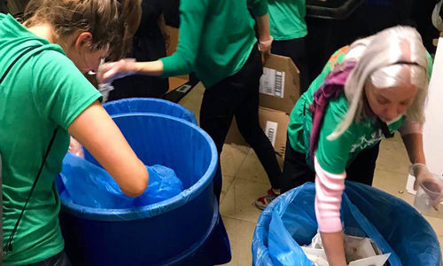 Two women wearing green shirts reaching into large blue recycling bins