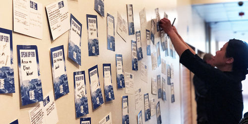 """A woman reaches up to tape a postcard to a wall covered in similar postcards, all reading """"Speak up for"""" with different words written in."""