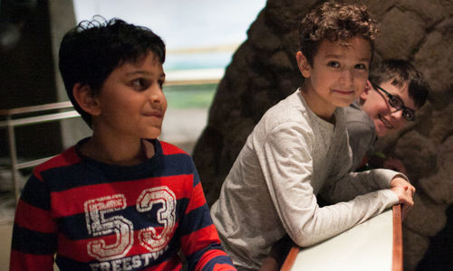Three boys smiling in Ancient Egypt exhibition