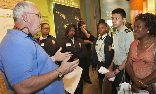 Docent leading high schoolers on tour through Restoring Earth exhibition