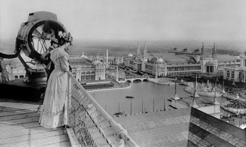 Two men and a woman stand on a roof, overlooking the World's Columbian Exposition, Chicago, 1893.