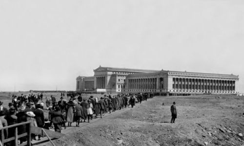 Opening Day of The Field Museum, May 5 1921. Crowds approaching the Museum with a lone man standing to the side of the crowd. People crossing a wooden bridge, with the entire exterior view of the north facade of the Museum in the background.
