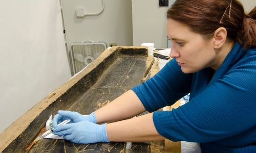 Conservator works on an Egyptian coffin.