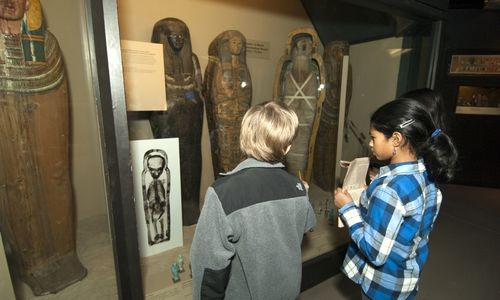 Two students viewing sarcophagi and a mummy in a display case.